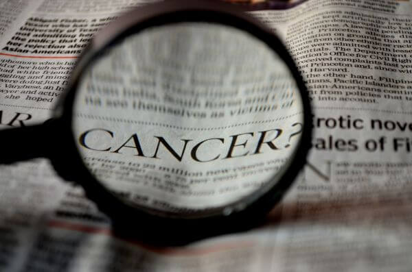 Cancer Word Magnified In Newspaper photo