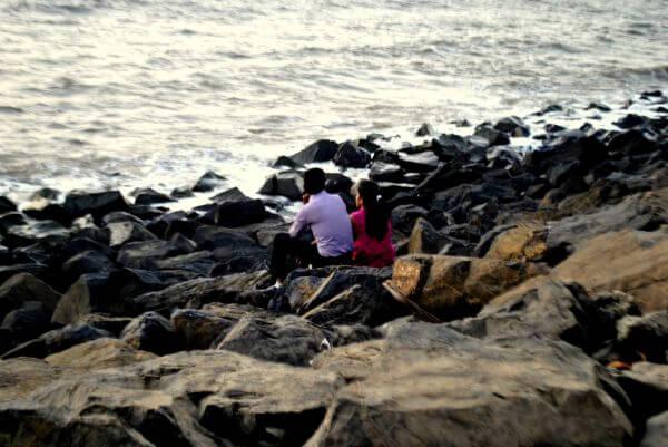 Couple Sitting Rocks Sea photo
