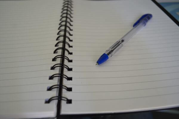 Pen On Spiral Ruled Paper Notebook photo