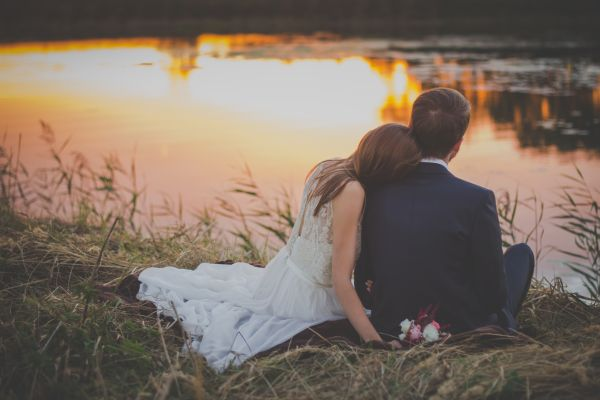 Wedding Couple on Grass at Sunset photo