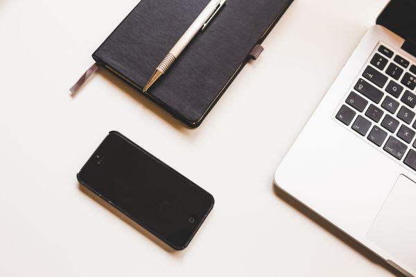 Black iPhone, MacBook & Notepad photo