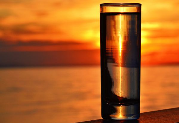Water Glass by the Sea with Sunset Background photo