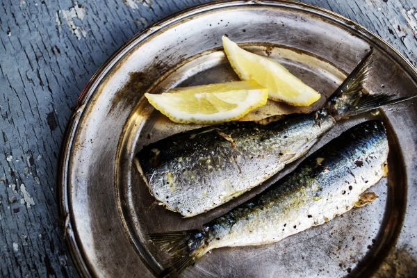 Sardines and Lemon on a Metal Plate with Broken Paint Wooden Background photo