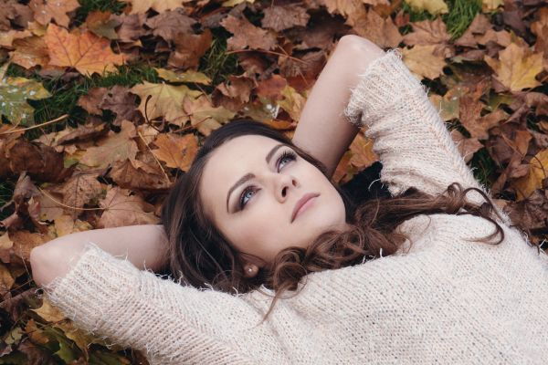 Beautiful Girl Portrait Lying on the Autumn Leaves in the Park photo