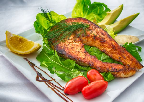 Plated Grilled Salmon Slice with Cherry Tomato, Lemon, Dip and Avocado photo