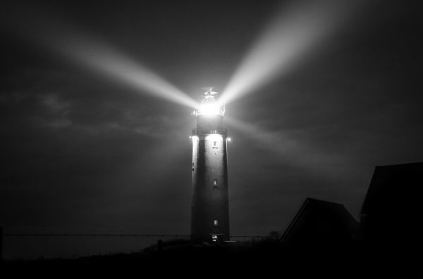 Lighthouse at night in black and white photo